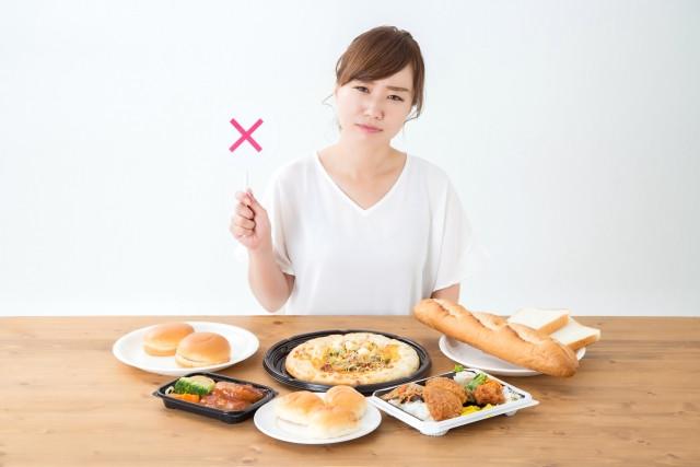 パンなどの食べ物の前で×を持っている女性